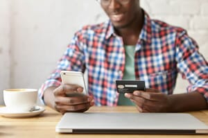 african american male marking purchase from iphone with credit card